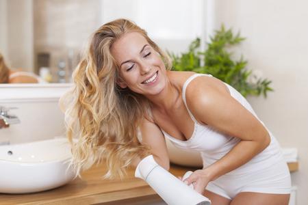Beautiful blonde woman enjoyment during drying hair photo