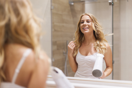 Blonde woman drying hair in front of mirror photo