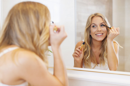 woman mirror: Lovely woman applying mascara in front of mirror  Stock Photo