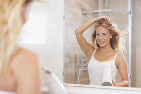 morning routine: Natural woman in front of mirror drying hair