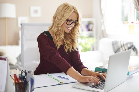 Blonde girl using laptop during studying at home  photo