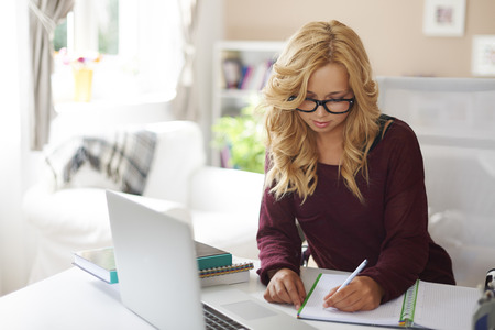 Blonde young girl doing homework after school photo
