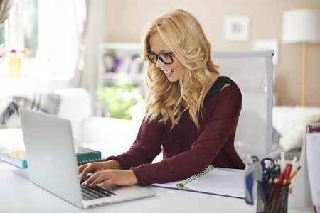 Blonde woman using laptop at home   photo