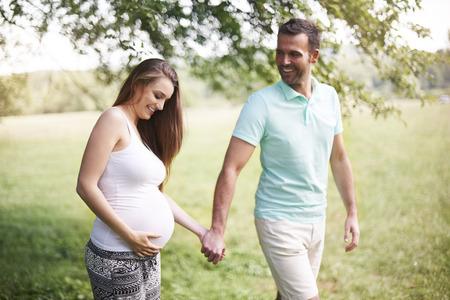parejas caminando: Mujer embarazada con el marido caminando en la pradera