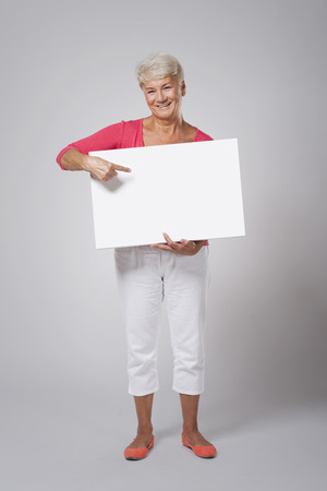 Happy senior woman pointing at whiteboard  photo