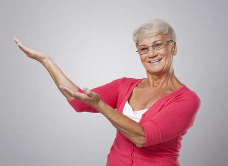 Cheerful senior woman showing at copy space  photo