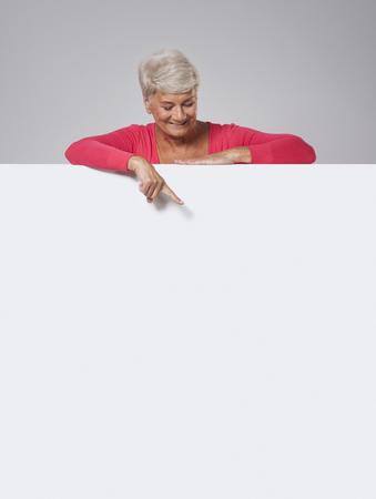 Senior woman peeking on whiteboard  photo