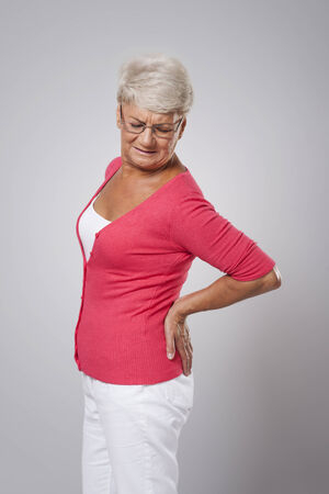 Senior woman with huge back pain  photo