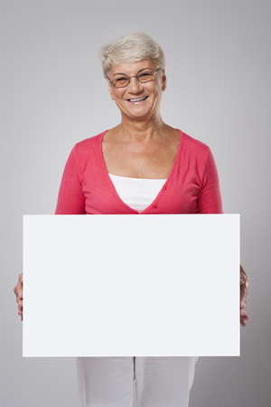 Lovely senior woman covering by whiteboard  Stock Photo