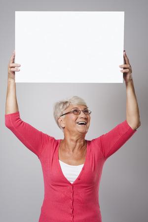 Beautiful senior woman holding whiteboard over the head  photo