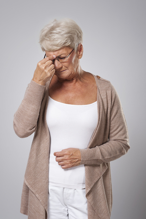 emotional stress: Senior woman suffering from strong headache Stock Photo