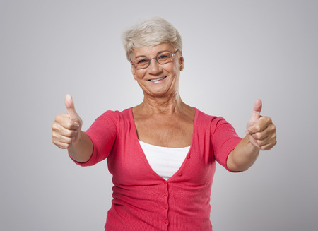 Successful senior woman with thumb up  photo