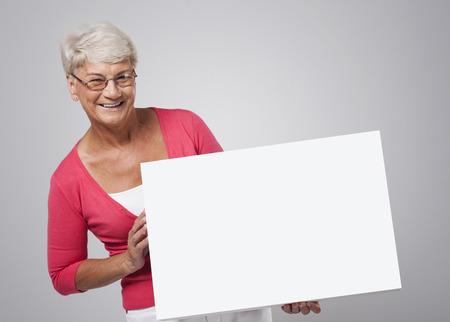 billboard posting: Smiling senior woman holding whiteboard  Stock Photo