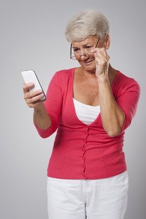 one senior woman only: Senior woman trying to use contemporary mobile phone