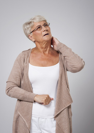Senior woman suffering from pain of neck Stock Photo