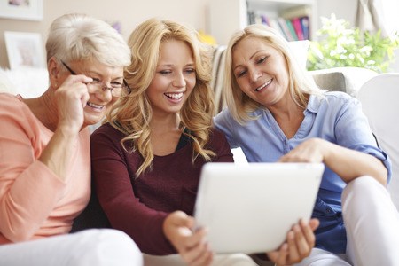 three generations: Loving family of women using digital tablet