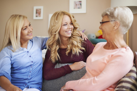 affectionate actions: Happy family women talking together at home
