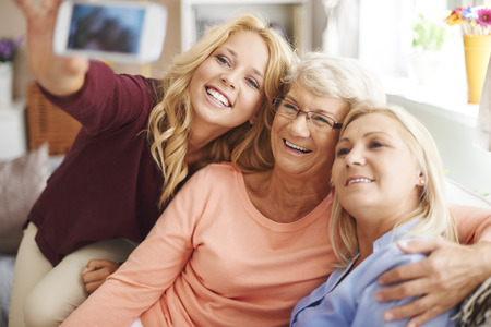 grandmother grandchild: Blonde girl taking selfie with mom and grandma Stock Photo