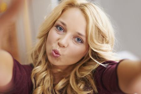 playful behaviour: Lovely blonde girl taking selfie  Stock Photo