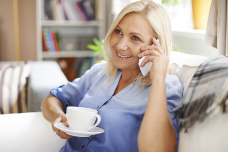 Relaxed mature woman enjoying conversation on mobile phone  photo