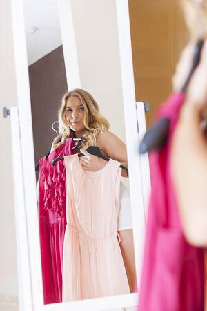 vistiendose: Mujer rubia de elegir el vestido para hoy