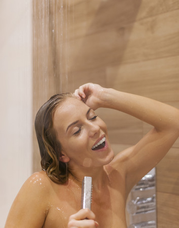 Beautiful woman singing under the shower  photo