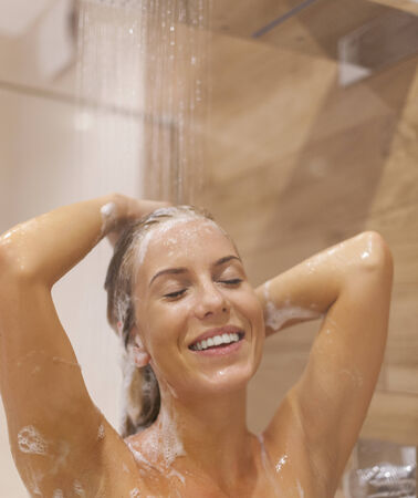 nude wet: Young woman washing hair under the shower Stock Photo