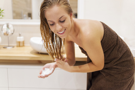 hair wrapped up: Woman applying conditioner after the shower   Stock Photo