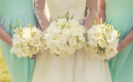 flowers close up: Bride with bridesmaids holding wedding bouquets Stock Photo