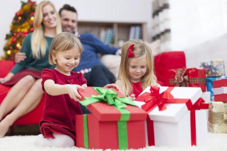 ni�as peque�as: Dulces ni�as abren regalos de Navidad Foto de archivo