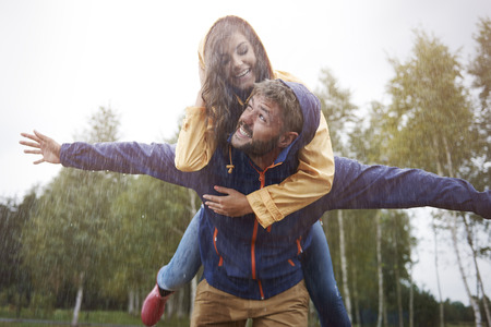 couple in rain: Playing in the rain like a child