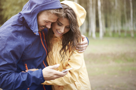 couple in rain: Let check the weather on smartphone Stock Photo