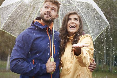 lluvia paraguas: Feliz pareja durante la lluvia Foto de archivo