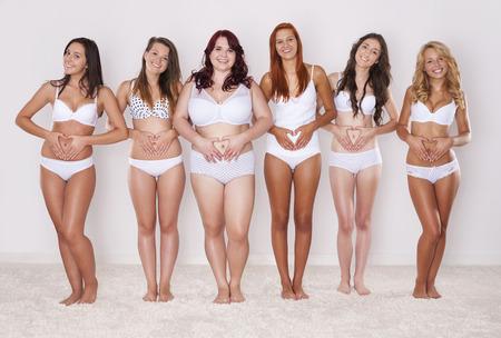 Groep vrouwen toont hartvorm op de buik