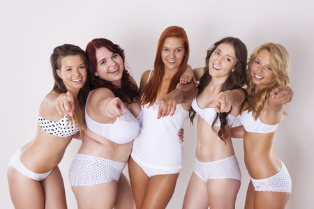 Happy group of girls in underwear pointing towards camera