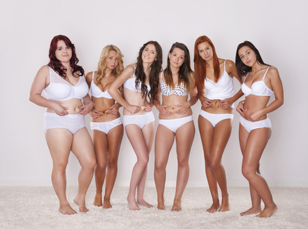 Group of happy women in underwear showing their fat belly  Stock Photo