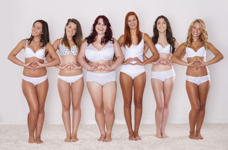 body conscious:   Group of happy women showing their heart shape on their tummy   Stock Photo