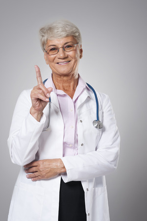Smiling senior doctor pointing by finger photo