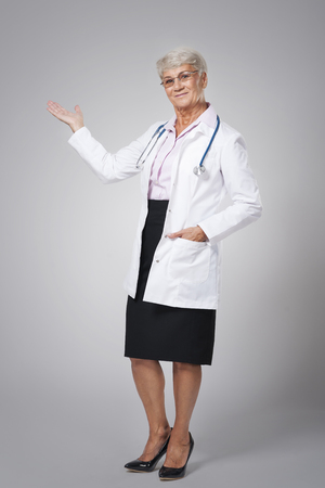 Smiling female doctor pointing at copy space photo