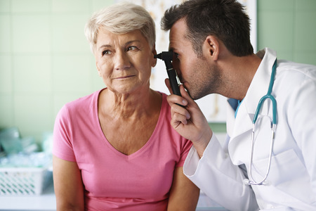doctor examining woman: Doctor examining ear of senior woman