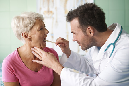Doctor checking throat of senior woman