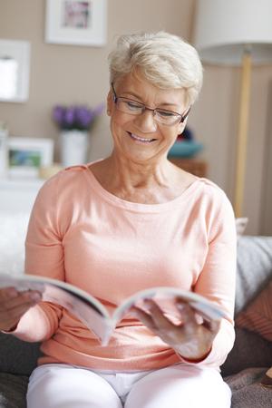 Senior woman reading magazine photo