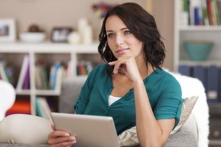 mujer pensativa: Mujer morena pensativo utilizando tableta digital en el hogar