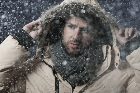 man looking up: Handsome man in snow storm Stock Photo