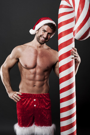 Delicious christmas candy cane with sexy man photo