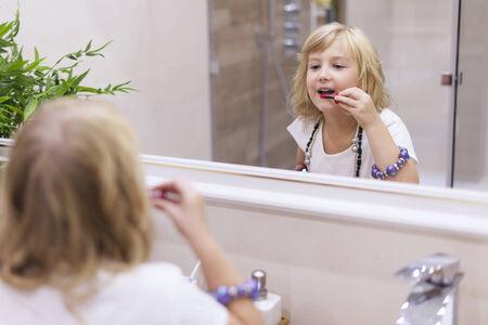 niños vistiendose: Niña que pone en maquillaje