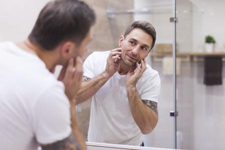 espejo: La comprobaci�n del estado del hombre de su piel en el espejo de reflexi�n Foto de archivo