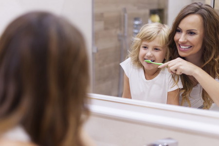 Morning lesson of brushing teeth with mommy photo