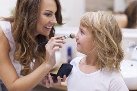 Mother and daughter putting on makeup Stock Photo