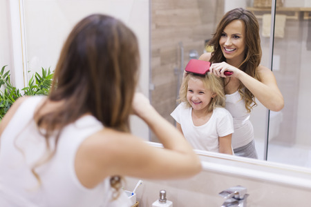combing: Mother brushing hair to her daughter Stock Photo
